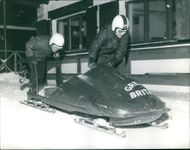 Prince Michael of Kent pushing a bobsled on the snow.