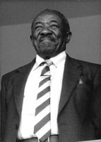Alfred Baphethuxolo Nzo in a portrait, smiling.