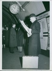 Clement Richard Attlee, 1st Earl Attlee, reading a newspaper while waiting for the train's arrival. 1955.