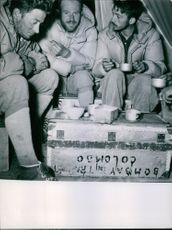 Men feeling cold having a tea in the camp.