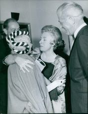 Janine Charrat hugging to a woman, smiling, with two men smiling while looking at them, 1963.