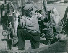 A man on a ship holding fishes on his both hands posing for camera.