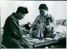 A man eats together with a woman who is holding a baby on her other hand.