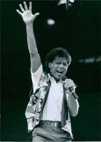 Cliff Richard standing while singing in the stage.