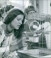 Woman with bird in cage.