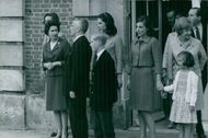 Princess Margaret standing with other people in street in front of a building and looking at something. 1967