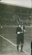A photo of a man standing in a football field.