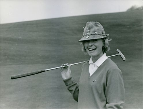 Pamela Tredinnick smiling while holding a golf club at the golf course.