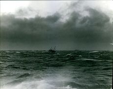 A ship sailing in the middle of the ocean, during a rainy day.
