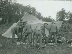 Military at their camp cutting some logs during field maneuver, 1931.
