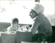 Farah Pahlavi with her son, sitting.