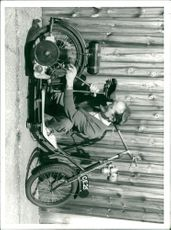 A man fixing his scooter.
