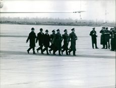 A photo of a group of police officers marching on the airport.
