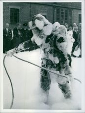 A fireman covered in foam while operating a machine that fights fire. 1967.