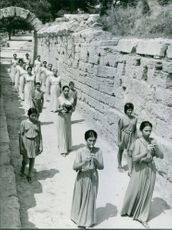 Women blowing pipes an and walking together.