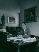 Somerset Maugham sitting at his desk in his study room at the Villa Mauresque.