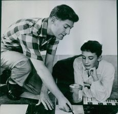 A male model points to the paper using a pen, the female model looks on.