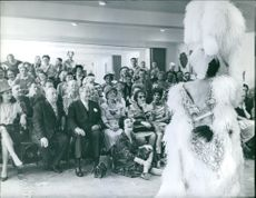People looking at woman in feather custume.   1961
