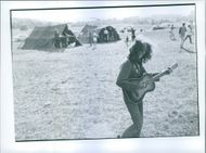 A lady playing a guitar in wide field.