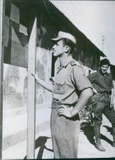 A German prisoner of war reading the bulletin board.