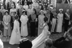 Farah Pahlavi walking on carpet and people looking at her.