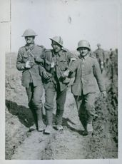 Soldiers walking in the field while helping the wounded soldier during Tyskland war.