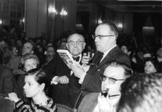 Henri Charriere with other men reading something.