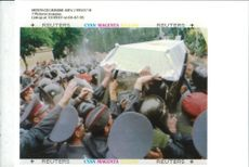 Ukrainian police shield themselves from a coffin.