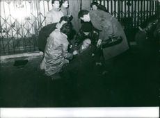 People helping a man who fainted on the street. Photo taken Feb.12, 1962.
