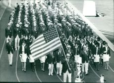 Man holding U.S. National Flag and leading the crowd during a parade.  Taken - Oct. 1964