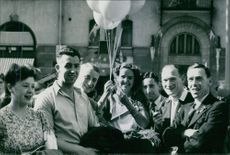 Men and women standing and smiling, holding balloon.