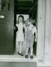 Princess Alexia of Greece and Denmark and a boy stepping out the door.