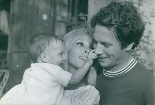 Dany Saval with a man and child, smiling.