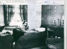 Woman lying on her bed and writing something on the paper.