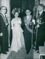 Royal man and woman coming out from the hall, while people looking and guard standing on both side of the door. 1954