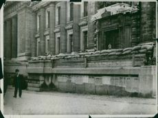 View of soldiers standing together behind the wall of a building and looking towards the camera.