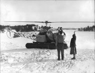 Fisherman Rolf Sjöblom with his wife Rigmor meets the postal delivery helicopter and pilot Captain Georg Carlsson at landing.