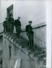 Policemen with a man stepping down from the stairs.