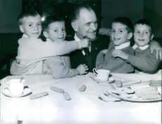 Man siting with children, having tea and cookies.