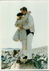 Couple standing on a big rock, embracing.