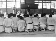 Karate practitioners, karateka, in their uniform sitting and listening to their karate master.