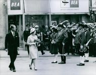 Elizabeth II holding a bouquet of flowers walks  with Prince Philip while people on the side watch them.