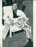 Kirk Douglas sitting on an outdoor chair.