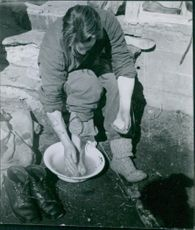 A man siting and washing his feet during Norwegian War. 1960