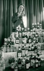 Margaret Thatcher poses with a large amount of bottles