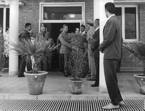 Mohammad Reza Shah Pahlavi shaking hand with police officers.