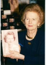 Margaret Thatcher poses with his book