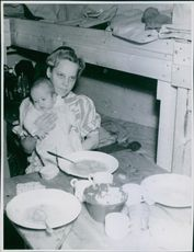 A woman carrying her baby while having a meal. 1945