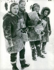 Girls holding wooden plank and posing on snow.