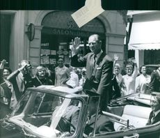 Prince Philip standing inside the car and waving his hand. 1972